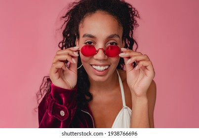 attractive black african american woman in stylish outfit velvet purple jacket and white top on pink studio background, summer fashion trend, happy smiling curly hair red sunglasses accessories