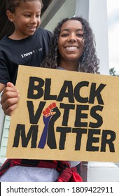 Attractive Black Female Activist Holding A Voter Suppression Sign with her Son