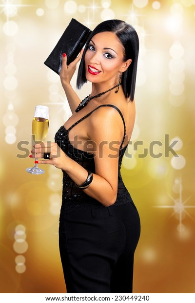 Attractive black hair woman holding glass of champagne, against gold background.
