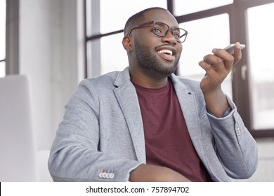 Attractive black male enterpreneur makes voice call for consulting about cash remittance, uses modern smart phone. Successful businessman discusses something with colleague via modern smart phone