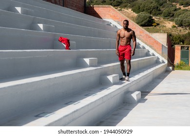 Attractive black muscular athletic man with sport clothing and bare chest walking along the stairway in a stadium after workout.