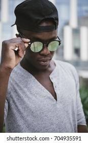 attractive black young man wearing reflective sun glasses