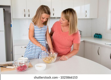 attractive blond 30s woman cooking and baking happy together with sweet adorable mini chef little girl at home modern kitchen in mother and daughter love education and family lifestyle concept