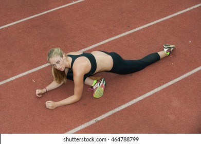 Attractive blond athlete stretching hip flexors on the track.