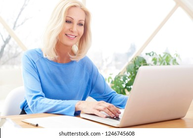Attractive blond businesswoman typing on laptop at office desk. Home office.