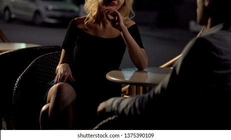 Attractive blond female seducing man on restaurant terrace, escort service