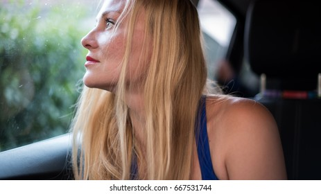 Attractive blond girl looks out the window of a car