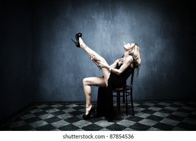 attractive blond in long black dress and ciggarette sit on chair indoor shot