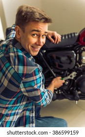 Attractive blond man in casual clothes is looking at camera and smiling while repairing a motorbike