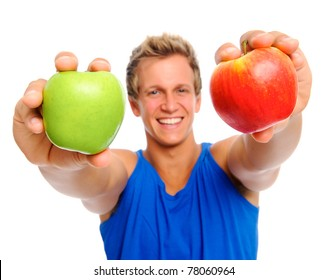 Attractive blond man holds out 2 apples; selective focus on fruit