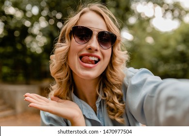 attractive blond smiling funny woman walking in park in summer outfit blue shirt taking selfie photo on phone, wearing elegant sunglasses, street fashion style