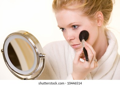 Attractive blond woman applying makeup wearing white robe with a round make up mirror in front