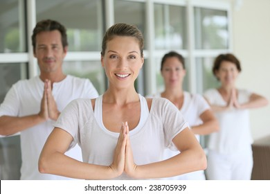 Attractive blond woman attending yoga course with group