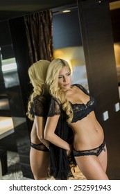 Attractive blond woman by the mirror