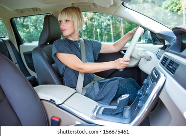 attractive blond woman driver looking back and parking her car