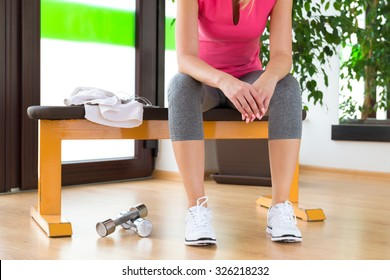 Attractive blond woman exhausted, resting after gym workout