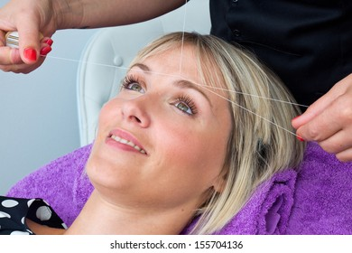 attractive blond woman having threading hair removal procedure