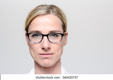 Attractive blond woman with her hair tied neatly back wearing glasses looking directly at the camera with a serious expression, close up head shot over grey with copy space
