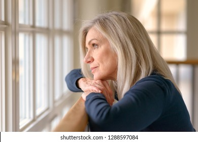 Attractive blond woman standing daydreaming as she stands resting her arms and chin on a wooden bannister staring out of a large window