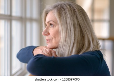 Attractive blond woman watching through a window with a serious expression resting her chin on her hands as she leans on a wooden railing