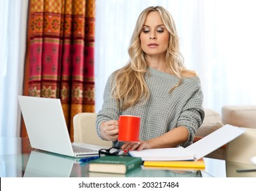 attractive blond woman writer sitting at the table and writing on the laptop computer