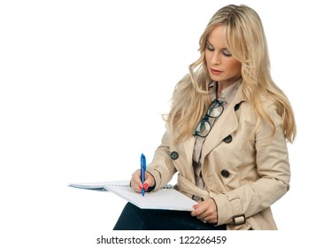 attractive blond woman writing in the notebook
