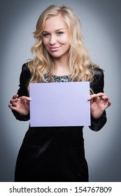 Attractive blond women holding a blank paper notice.