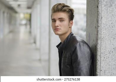 Attractive blond young man with leather jacket standing outside against pillar, looking down at camera
