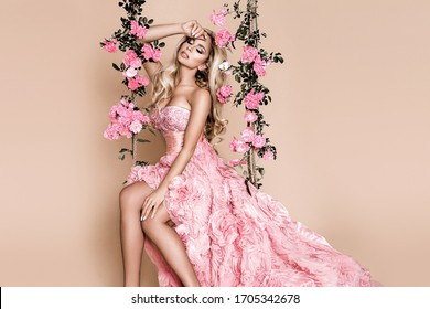 Attractive blonde beauty on a flower swing. Spring concept. Beautiful natural woman in elegant pink dress on a flower swing. Wedding fashion and bride concept.