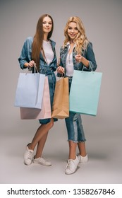 attractive blonde and brunette women in denim clothes holding shopping bags and looking at camera
