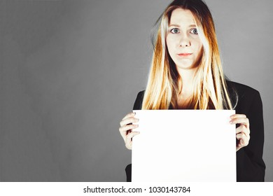 Attractive blonde business woman holding white banner with copy space for additional text or graphic. Frustrated model. Girl is posing on a grey background
