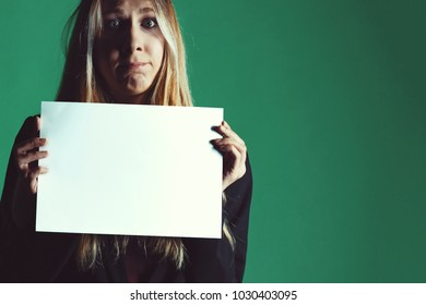 Attractive blonde business woman holding white banner with copy space for additional text or graphic. Confused model. Girl is posing on a green background