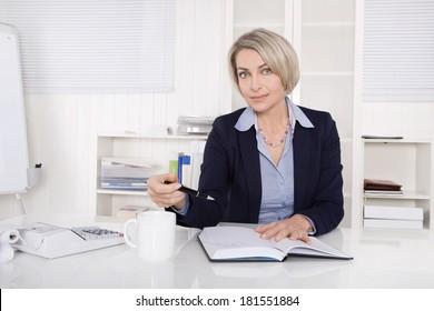 Attractive blonde businesswoman sitting at desk.