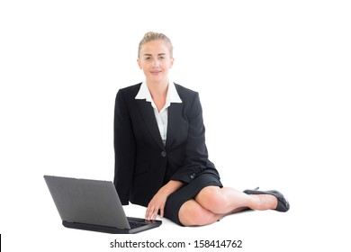 Attractive blonde businesswoman sitting on floor using her notebook looking at camera