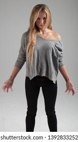 Attractive Blonde Caucasian Girl wearing Sweater, dramatic summoning pose