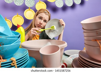 attractive blonde dishwasher holding a plate and brush, sitting behind the table with a pile of dirty cutlery, hard work, housekeeping