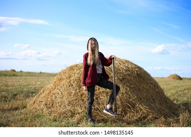 Attractive blonde farmer girl, in a burgundy sweater, stands near a pile of hay in a field with a pitchfork in her hands. She had a hard working day.