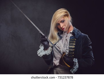 An attractive blonde female dressed in medieval urban clothes holds a silver sword over grey background.