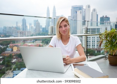 Attractive blonde female freelancer making remote job during vacation creating content for blog and websites to attract customers and followers to increase incomes from sales using laptop and wifi