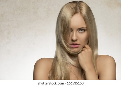 attractive blonde female posing in beauty shoot with perfect skin, naked shoulders and long silky smooth hair