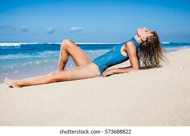 Attractive blonde female in swimwear lying down at the beach with blue deep water at background