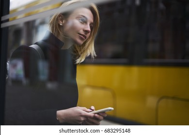 Attractive blonde female tourist waiting for public transport on bus stop using application for navigating in city, charming hipster girl browsing information for traffic in town via smartphone
