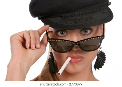 Attractive blonde female wearing black baret smoking cigarette, looking with beautiful eyes over sunglasses