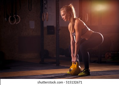 Attractive blonde girl doing exercises with kettle bell. Weightlifting, cross fit and power lifting workout. Sports, fitness concept.
