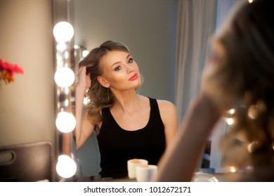 Attractive blonde girl primp at the mirror with lamps in the beauty studio. A happy satisfied customer of make-up and hairstyle service. Closeup beautiful face with natural makeup and luxurious curls.