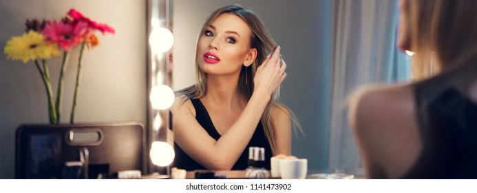 Attractive blonde girl primp at the mirror with lamps in the beauty studio. A happy satisfied customer of make-up and hairstyle service. Beautiful face with natural makeup and straight hair.