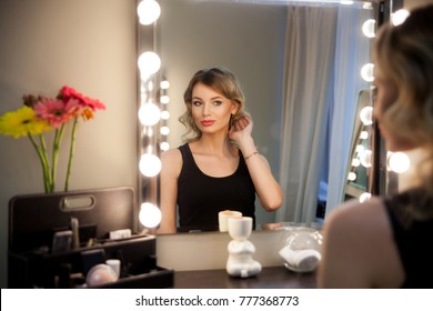 Attractive blonde girl primp at the mirror with lamps in the beauty studio. A happy satisfied customer of make-up and hairstyle service. Beautiful face with natural makeup and luxurious curls.