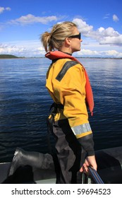 Attractive blonde girl at sea wearing a dry suit and life jacket