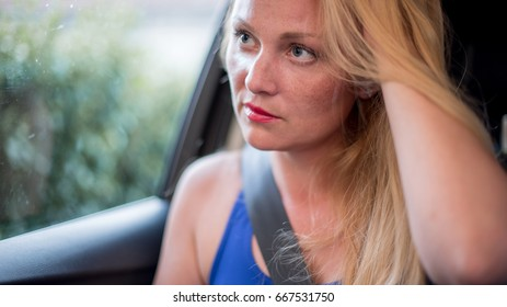Attractive blonde girl sitting in the car
