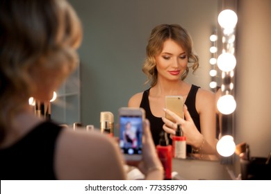 Attractive blonde girl take selfie with a phone at the mirror with lamps in the beauty studio. Beautiful face with natural makeup and luxurious curls.
